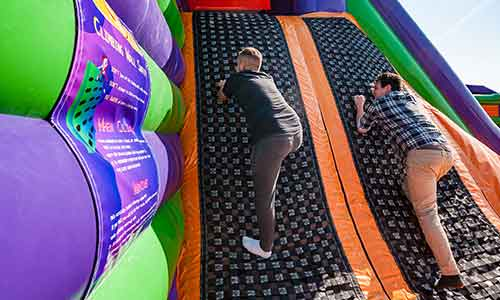 Two guys climbing the wall at the inflatable jump park in Foxboro Massachusetts