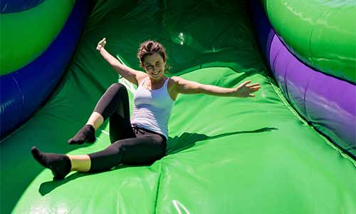 Woman coming down the big step slide at the inflatable jump park in Foxboro Massachusetts