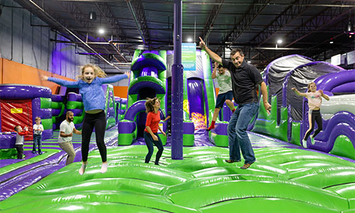 Family having fun together bouncing on the soft inflatable indoor jump park in Londonderry New Hampshire