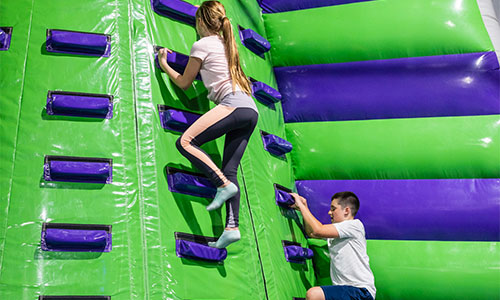 Young teens climbing the inflatable mountain.