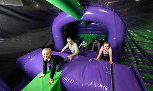 Adults and children climbing up a tunnel at the airpark