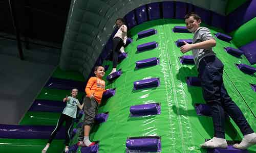Children climbing an inflatable wall at the airpark at XtremeCraze in Londonderry NH